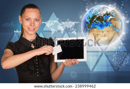Beautiful businesswoman holding blank tablet PC and blank business card in front of PC screen. Globe, world map, network with people icons, triangles and other virtual elements as backdrop. Elements - stock photo