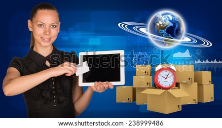 Beautiful businesswoman holding blank tablet PC and blank business card in front of PC screen.Beside are commodity boxes and alarm-clock on top of one of them. Globe surrounded by rings, graphs and - stock photo