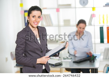 Beautiful  businesswoman holding clipboard with colleague on background - stock photo