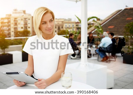 Beautiful businesswoman holds digital tablet and looks away while she sits in modern coffee shop outdoors, charming female restaurant owner uses portable touch pad and waits clients on a breakfast - stock photo