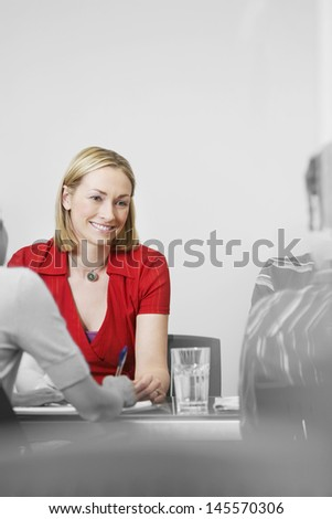 Beautiful businesswoman in red at a meeting - stock photo