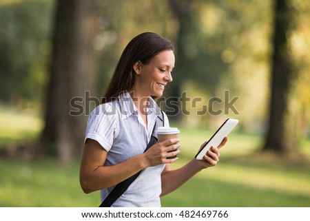 Beautiful businesswoman is drinking coffee and using digital tablet while resting from work at the park.Businesswoman drinking coffee and using digital tablet