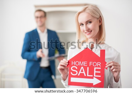 Beautiful businesswoman is selling her apartment. She is holding a billboard with home for sale. The lady is smiling. The estate agent is standing on background