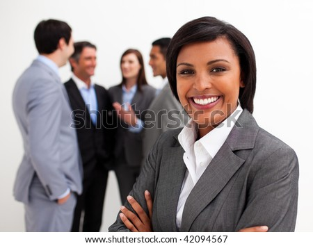 Beautiful businesswoman leading her team agaisnt white background - stock photo