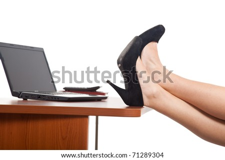 Beautiful businesswoman legs laying on the desk in front of a laptop