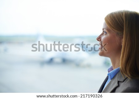 Beautiful businesswoman looking through window in airport - stock photo