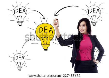 Beautiful businesswoman makes sketch of idea on whiteboard - stock photo
