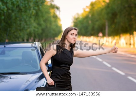 Beautiful businesswoman on the road  trying to stop another car