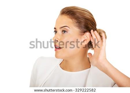 Beautiful businesswoman overhears a conversation. - stock photo
