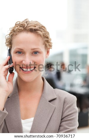 Beautiful businesswoman phoning in her office - stock photo