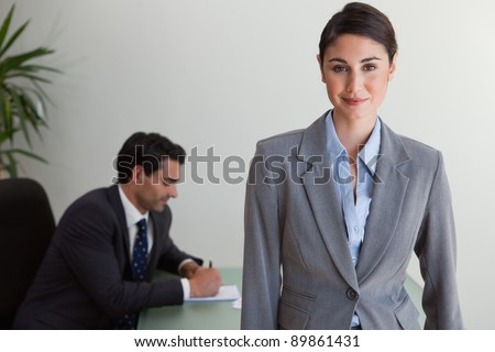 Beautiful businesswoman posing while her colleague is working in an office - stock photo