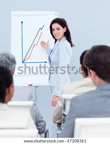 Beautiful businesswoman reporting sales figures to her team - stock photo
