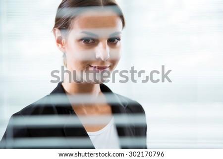 Beautiful businesswoman's portrait. View through blinds - stock photo
