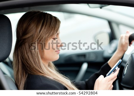 Beautiful businesswoman sending a text while driving to work - stock photo