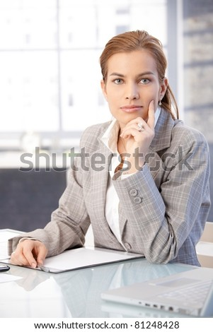 Beautiful businesswoman sitting at desk in office, thinking.?