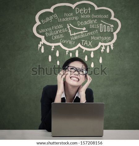 Beautiful businesswoman sitting in front of her laptop worry about the debt crisis  - stock photo