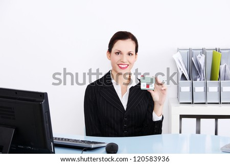 Beautiful businesswoman sitting in the office holding little house.