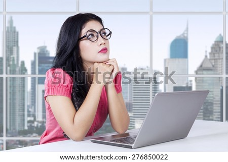 Beautiful businesswoman sitting in the office with laptop computer on the table and looks thinking something - stock photo