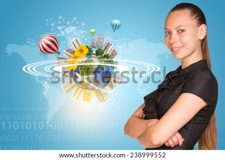 Beautiful businesswoman smiling and looking at camera. Beside is miniature Earth with trees, flowers, industrial and residential buildings, air balloons, airplane and surrounded by rings. Network with - stock photo