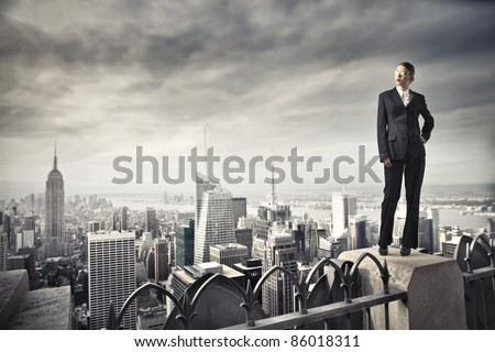 Beautiful businesswoman standing on the rooftop of a skyscraper