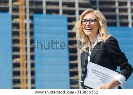Beautiful businesswoman toothy smiling with clipboard in her hands. Lady in business suit and glasses is an owner of the building behind her. - stock photo