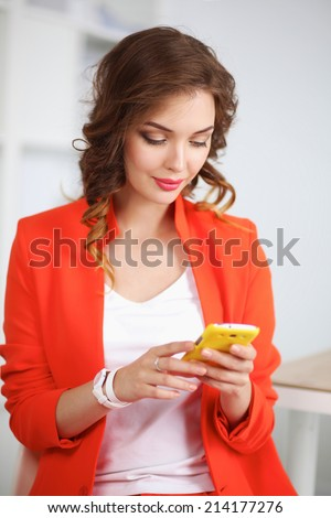 Beautiful businesswoman using cell phone standing in office - stock photo