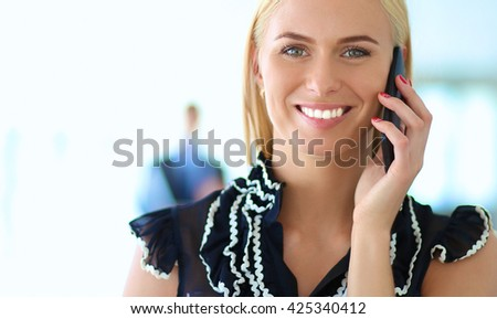 Beautiful businesswoman using cell phone , standing in office - stock photo