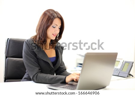 Beautiful businesswoman using laptop in her office