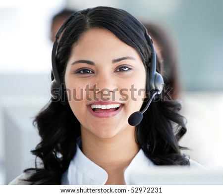 Beautiful businesswoman wearing a headset to talk with customer in the office - stock photo