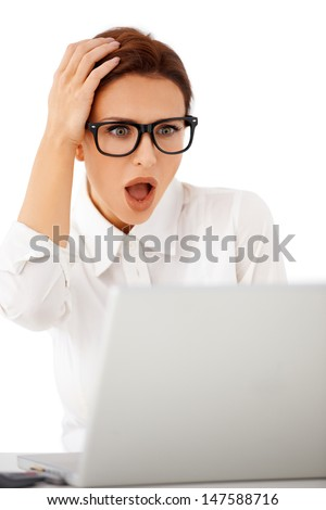 Beautiful businesswoman wearing glasses looking at her laptop in horror with her hand raised to her head and mouth open - stock photo