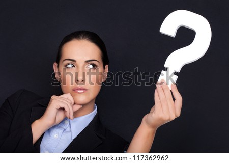 Beautiful businesswoman with a thoughtful expression holding a white question mark in her hand against a black studio background - stock photo