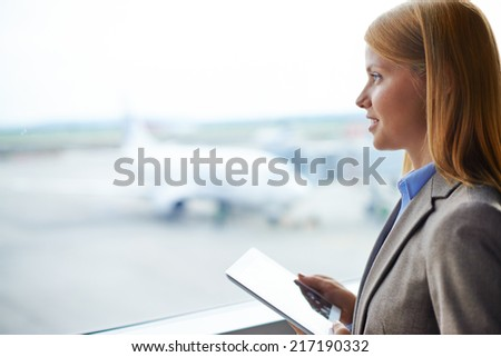 Beautiful businesswoman with digital tablet looking through window in airport - stock photo