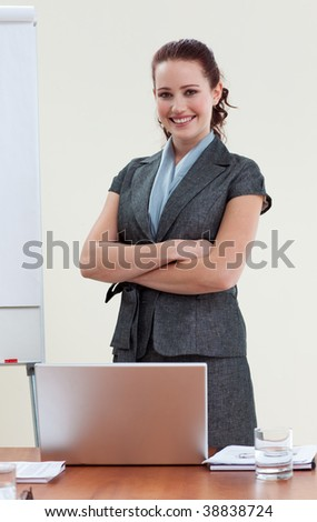 Beautiful businesswoman with folded arms in office smiling at the camera