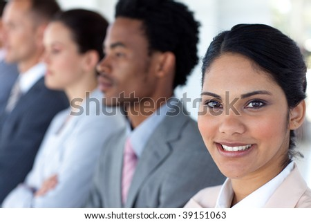 Beautiful businesswoman with her team in a line smiling at the camera
