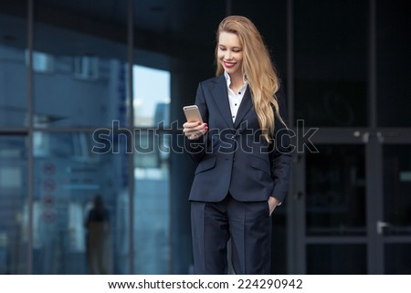 beautiful businesswoman with mobile on the background of the business center - stock photo