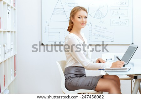Beautiful businesswoman working in the office with a laptop.  - stock photo