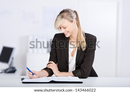 Beautiful businesswoman writes something on her notebook