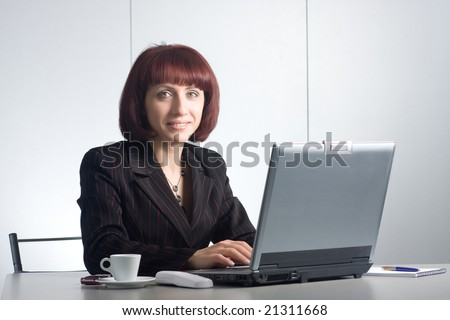 Beautiful businesswomen behind a desktop and a laptop - stock photo