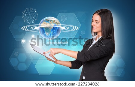 Beautiful businesswomen in suit using digital tablet. Earth with hexagons, graphs and wire-frame spheres. Element of this image furnished by NASA - stock photo