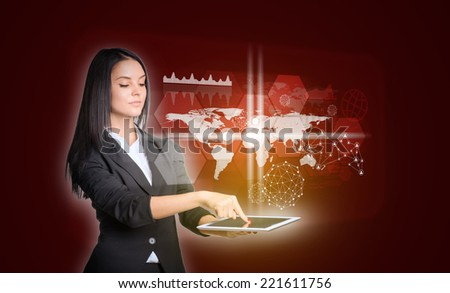 Beautiful businesswomen in suit using digital tablet. World map with transparent hexagons, graphs and network - stock photo