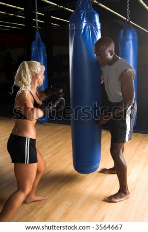 Beautiful but dangerous female fighter working with her trainer punching a heavy bag in an Mixed Martial Arts gym. - stock photo