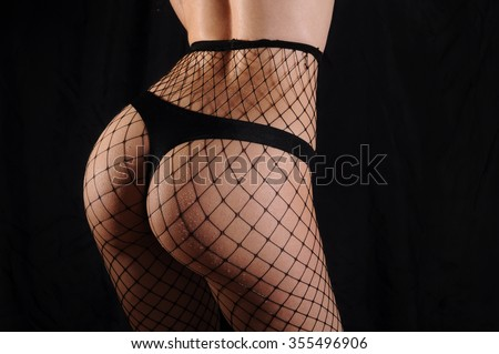 Beautiful buttocks of a woman wearing black panties and fishnet tights. Black background, back view.  - stock photo