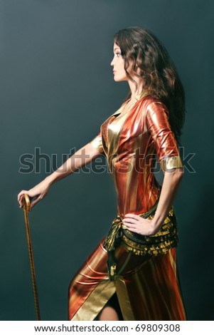 Beautiful cabaret woman in bright dress with stick. Oriental show dancer girl on black background. - stock photo