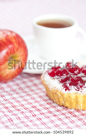 beautiful cake with berries,apple and tea on plaid fabric