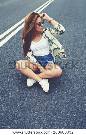Beautiful Californian hipster girl sitting on her cruiser long-board in the middle of asphalt road, fashion model posing with skate board wearing colorful sunglasses, copy space area for content - stock photo