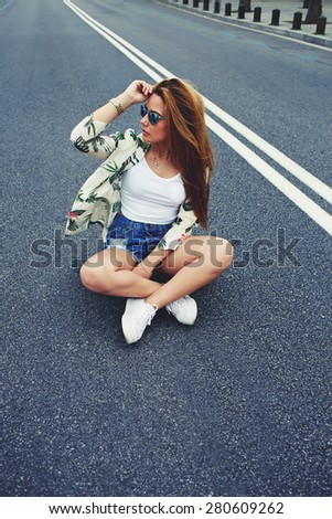 Beautiful Californian hipster girl sitting on her cruiser long-board in the middle of asphalt road, trendy fashion model posing with skate board wearing colorful sunglasses, summer time - stock photo