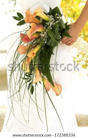 beautiful calla lillies on silk dress with hands wedding bouquet detail  - stock photo