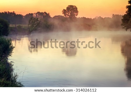 Beautiful calm river with the mist over the surface of the water at dawn by the light of the rising sun.