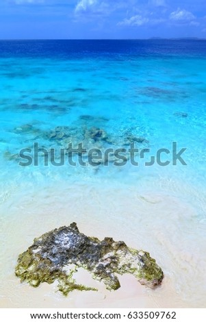 Beautiful calm sea and beach scenery. Tropical beach with stones, fine sand and azure cyan calm water surface. Vacation resort with romantic white beach. Summer holiday sea shore.