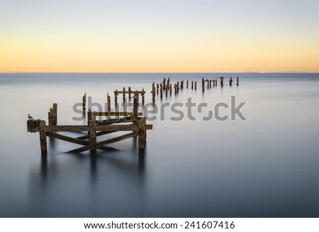 Beautiful calming long exposure landscape of ruined pier at sunset - stock photo